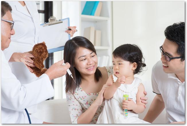 パパ・ママに連れられて予防接種を受ける赤ちゃん
