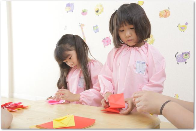 真剣に折り紙をする女の子