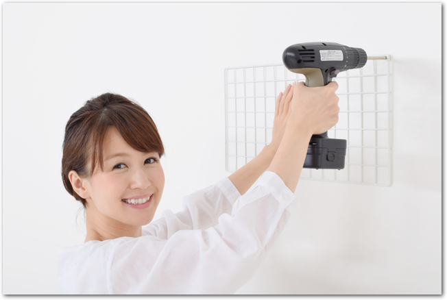 電動ドライバーを使ってワイヤーラックを取り付ける女性