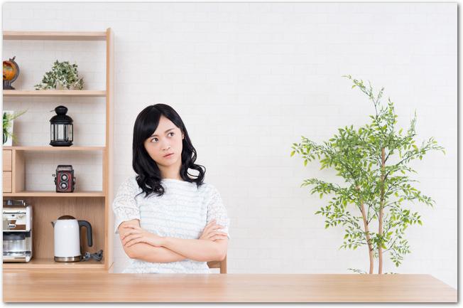 自宅のインテリアについて座って悩むようすの女性
