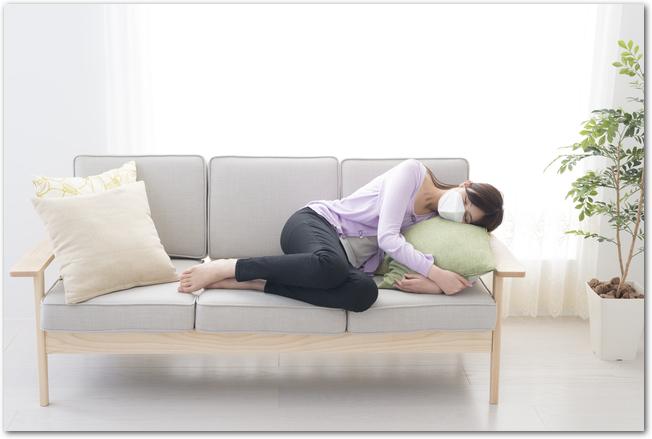 貧血でソファーに倒れ込む女性