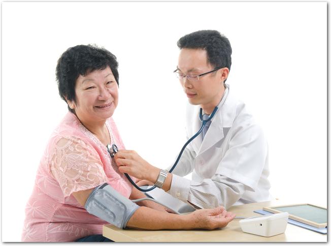 病院で血圧を測定してもらっている高年齢の女性
