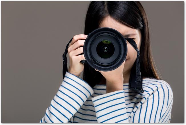 一眼レフで写真撮影をする女性