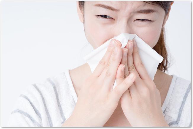 花粉症でつらそうに鼻をかむ女性