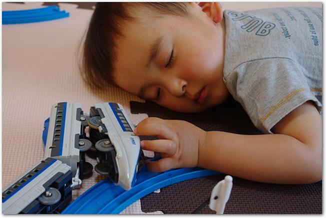 新幹線を夢見ながらお昼寝する幼い子ども