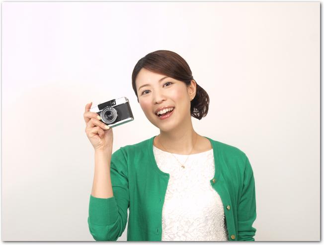 コンパクトデジタルカメラで撮影する女性