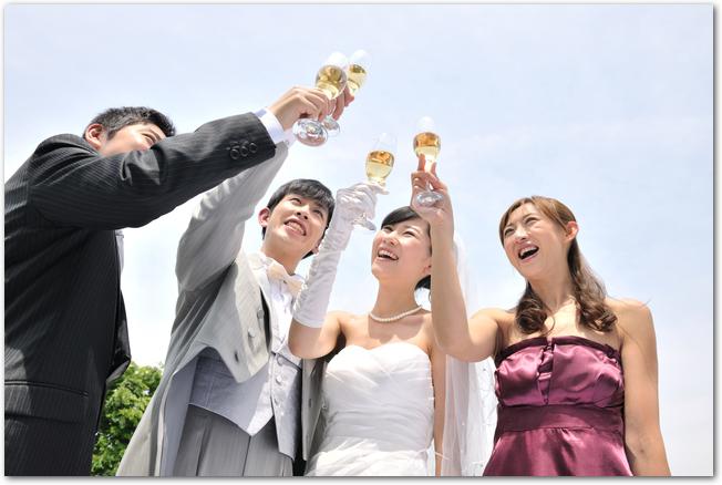 結婚式で屋外で乾杯をしている新郎新婦と友人
