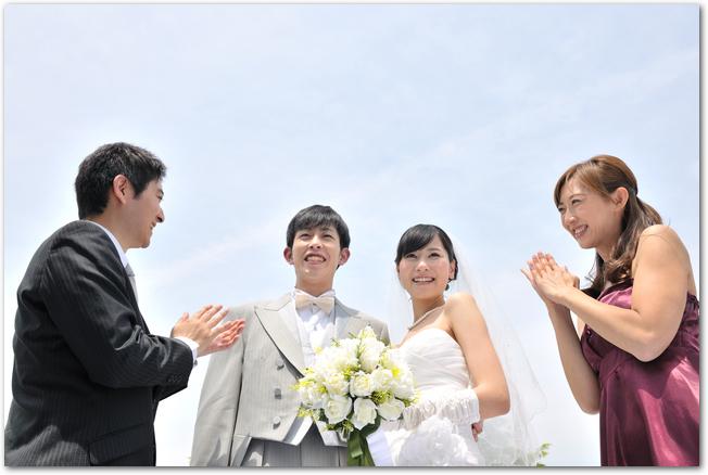 結婚式で新郎新婦とお祝いする友人男女