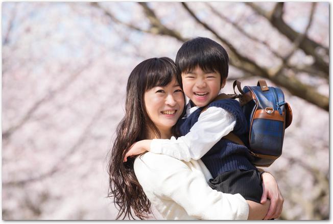 桜並木の下に立つ幼稚園児の男の子と母親