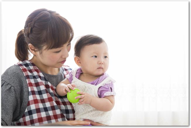 保育園で保育士さんに抱っこされる2歳児たち