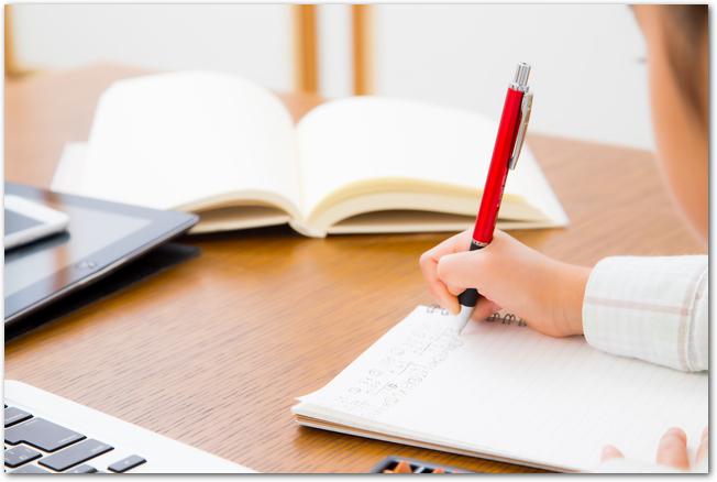 家の机で勉強をしている女の子の様子