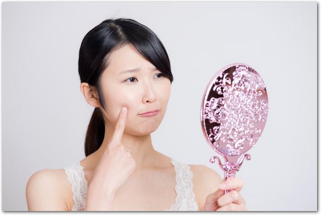 手鏡を見て肌荒れに悩む女性の様子