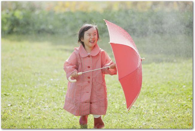 公園の芝生の水たまりを歩く長靴を履いた女の子の様子