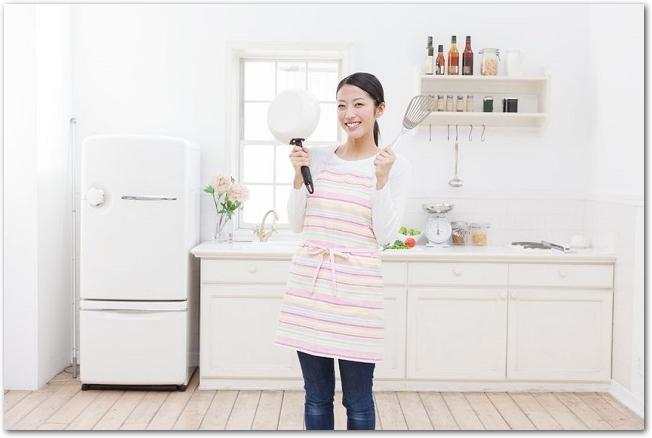 キッチンで調理器具を持つ笑顔のエプロン姿の女性