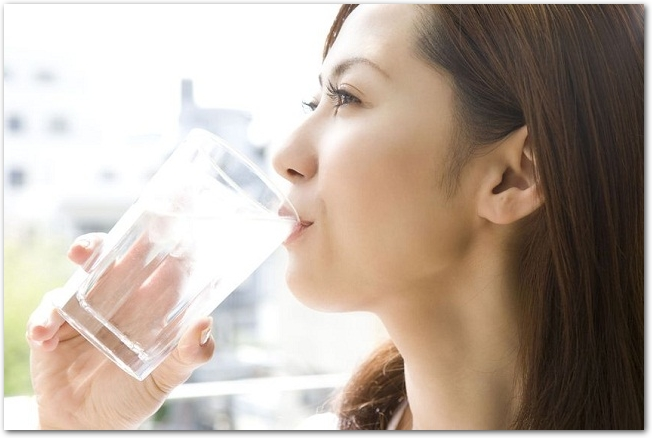 グラスの水を飲む若い女性の様子