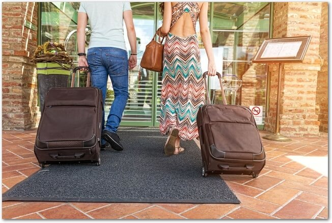 キャリーバッグを引きながらホテルの玄関に入るカップルの様子