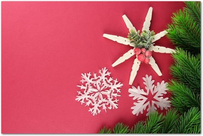 赤い背景に置かれたモミの木の枝と白い雪の結晶の切り紙