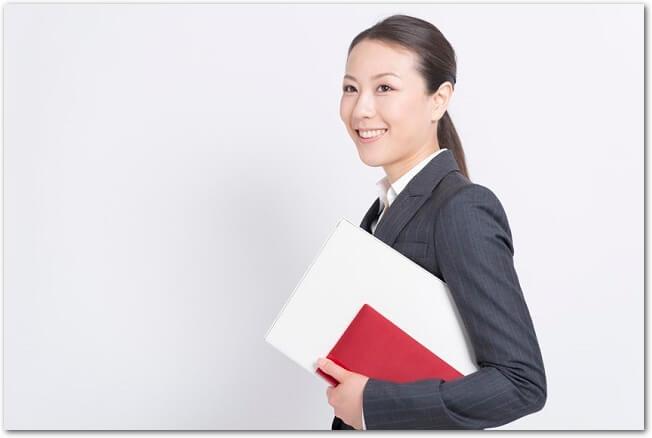 ファイルを持つスーツ姿の笑顔の女性の様子