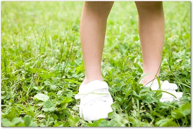 芝生の上に立つ白い靴を履いている女の子の足元