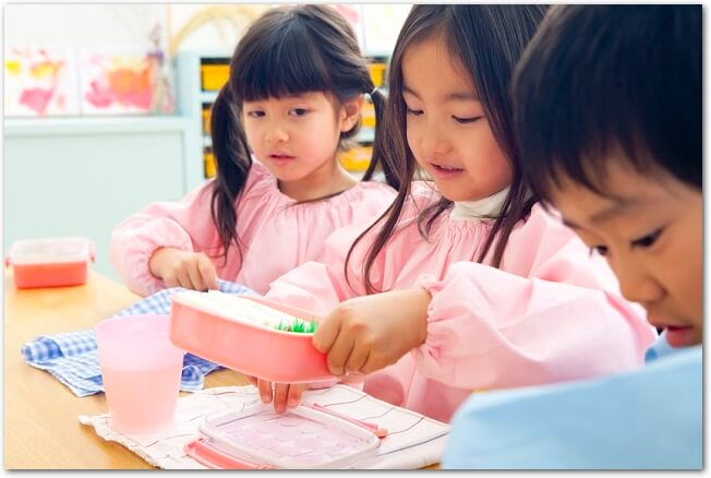 お弁当箱を開けている幼稚園児たちの様子